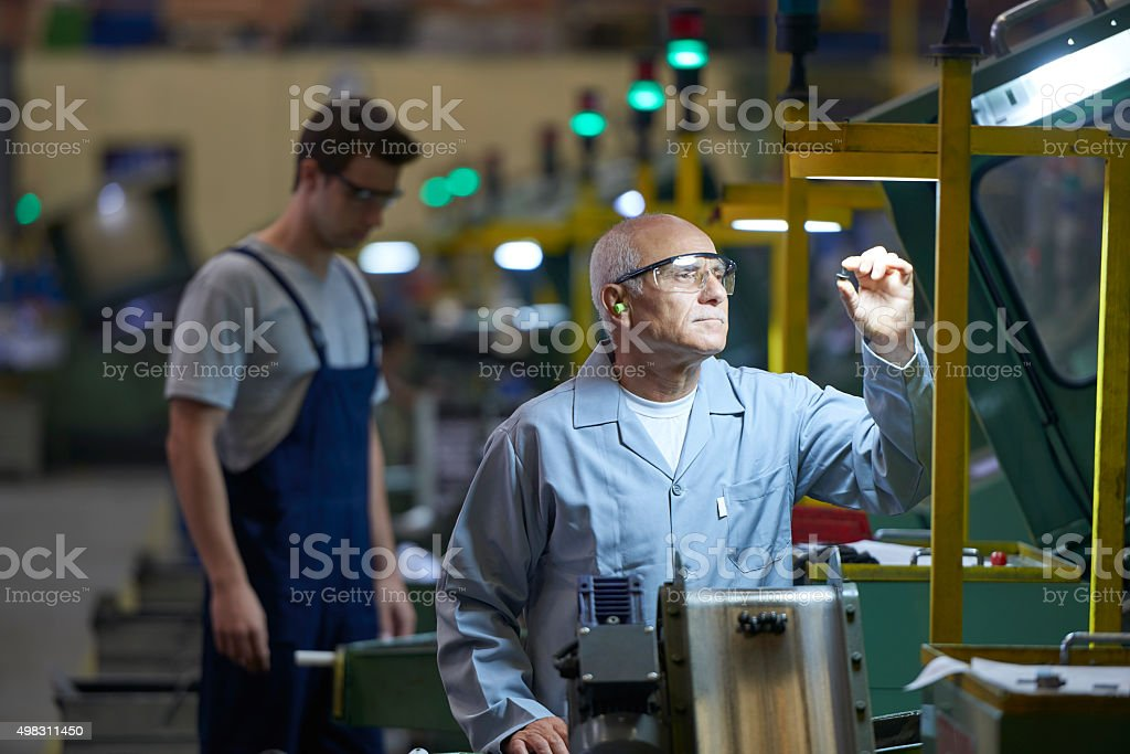 Worker looking at product in bolt factory stock photo