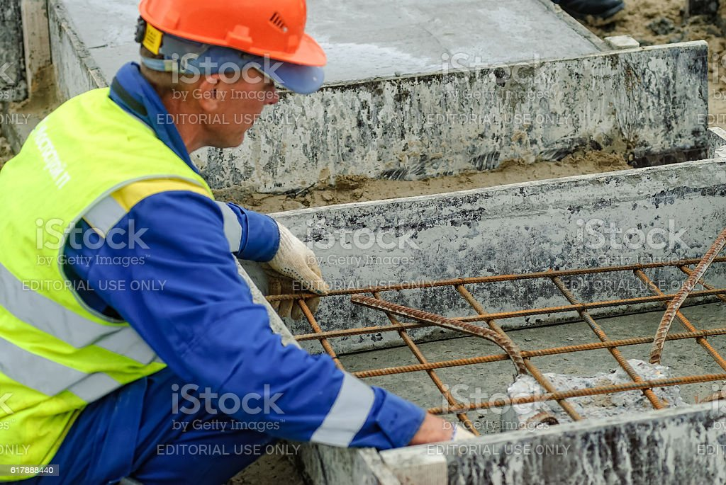 Worker makes base for big oil tank stock photo