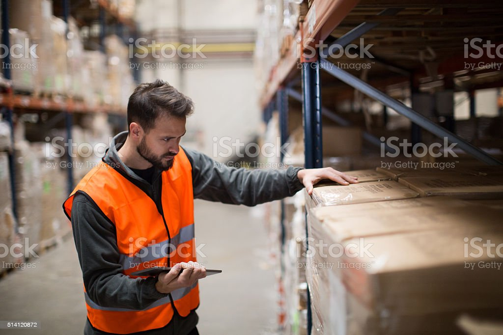 Worker making a checklist in a warehouse with digital tablet stock photo