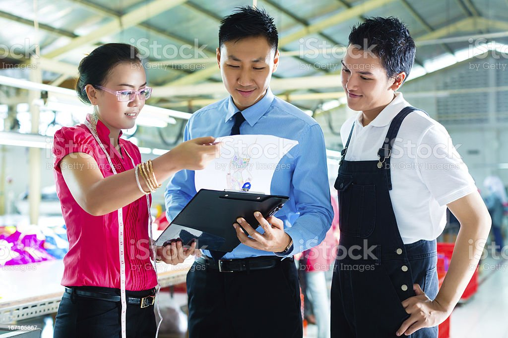 Worker, manager and designer in garment factory stock photo