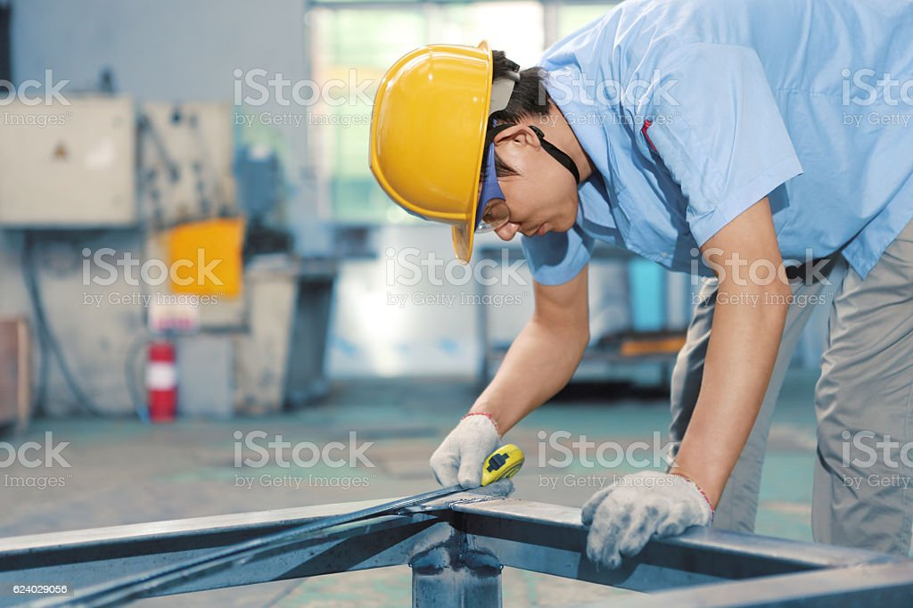Worker measuring steel with measuring tape stock photo