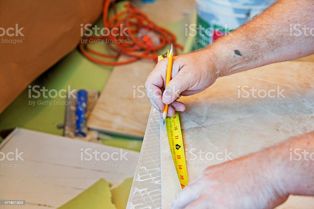 Worker measuring tile before cutting to size royalty-free stock photo