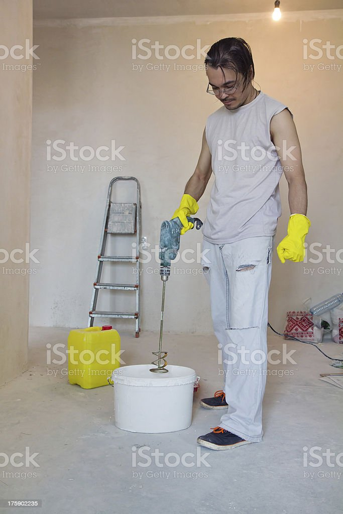 Worker mixing glue with a power drill royalty-free stock photo