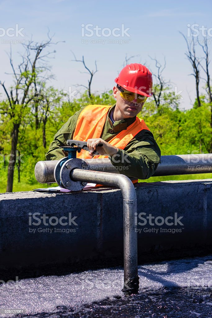 Worker monitor filtering industrial water stock photo