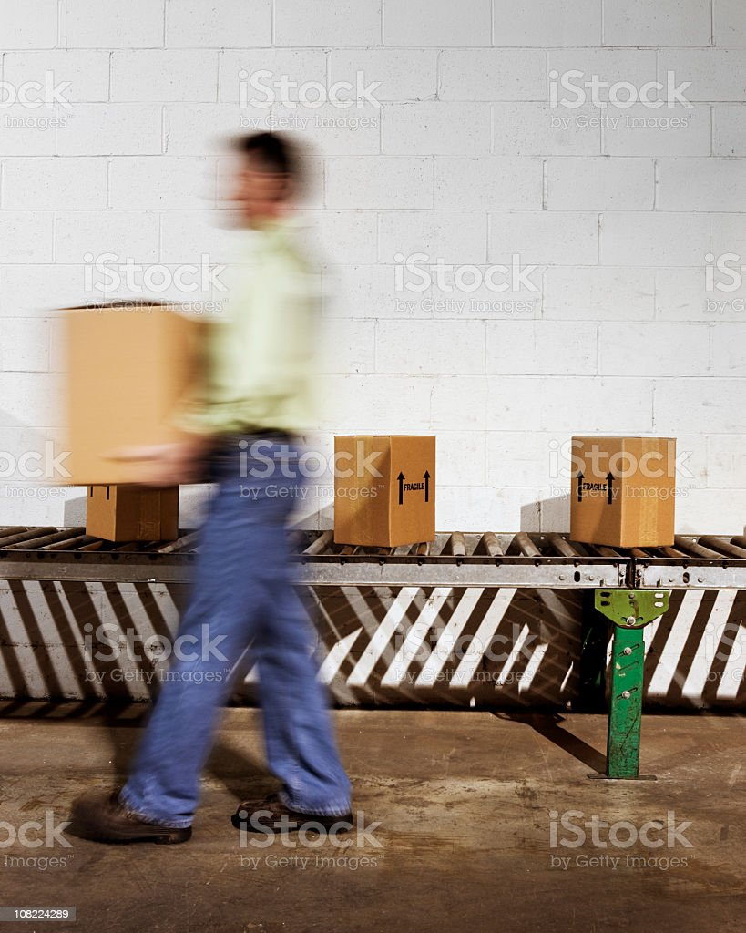 Worker moving shipping boxes off conveyor belt. royalty-free stock photo