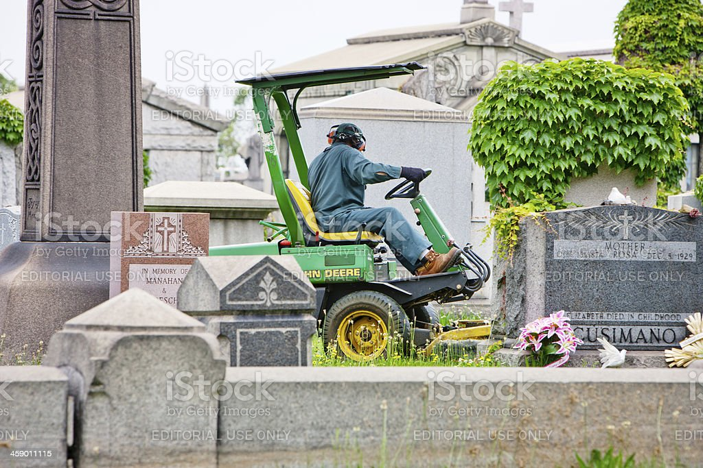 Worker mowing lawn on Calvary Cemetery, New York stock photo