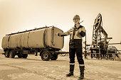 Worker near pumpjack and tank trailer in the oilfield.