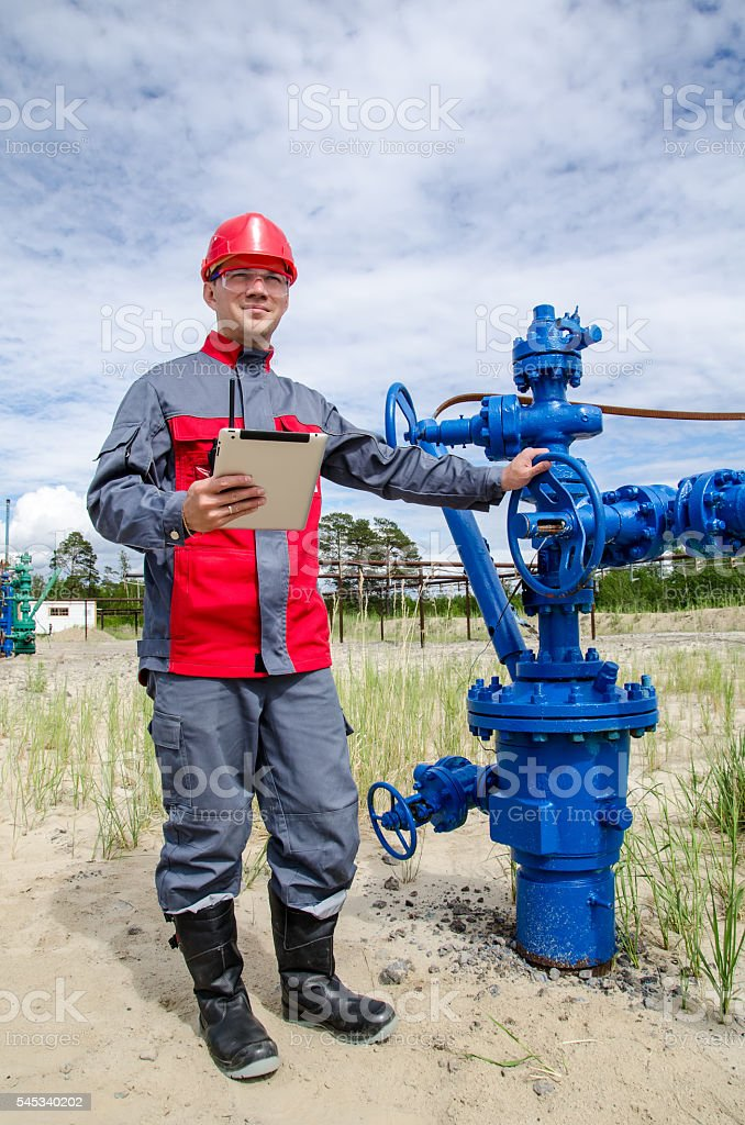 Worker near well head valve stock photo