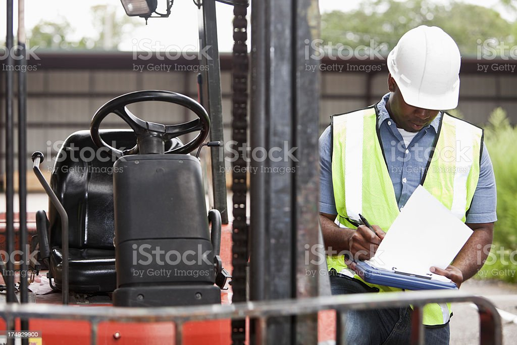Worker next to forklift writing on clipboard stock photo