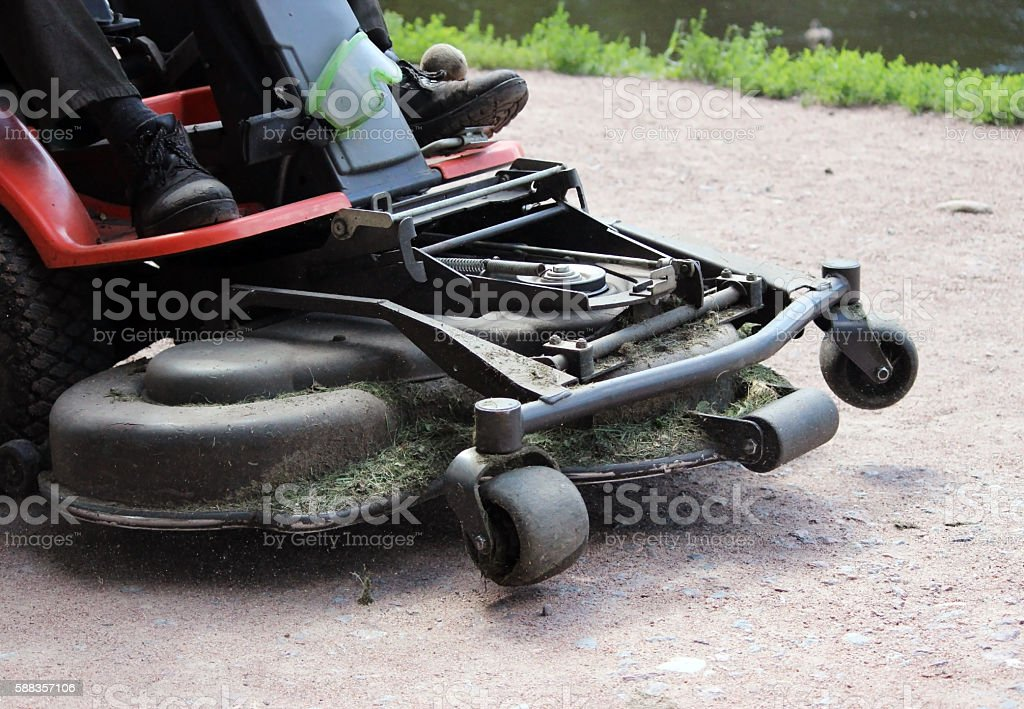Worker of park rides on the mower  gravel road. stock photo