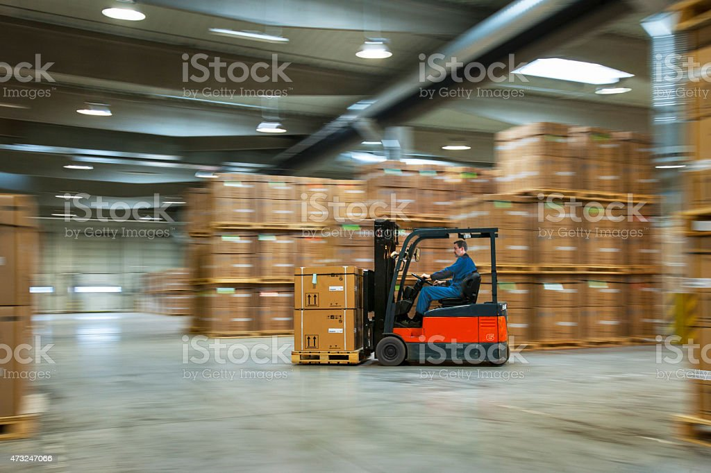 Worker on a lift truck arranging boxes in industrial warehouse stock photo