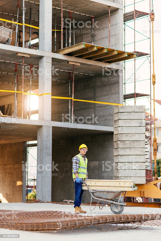 Worker on construction platform with wheelbarrow stock photo