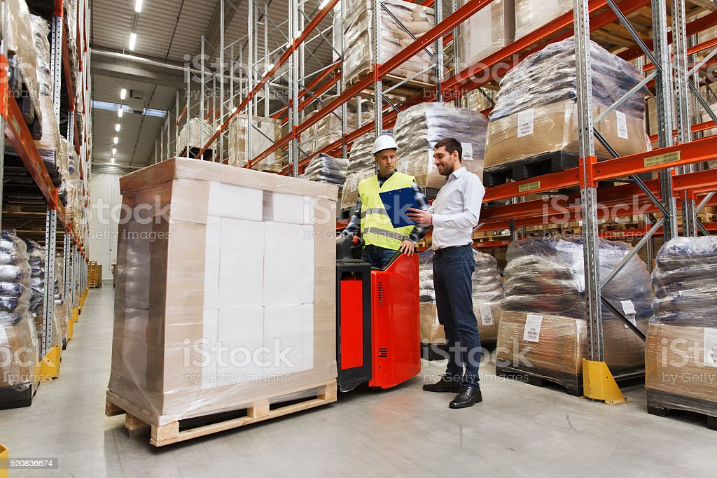 worker on forklift and businessman at warehouse stock photo
