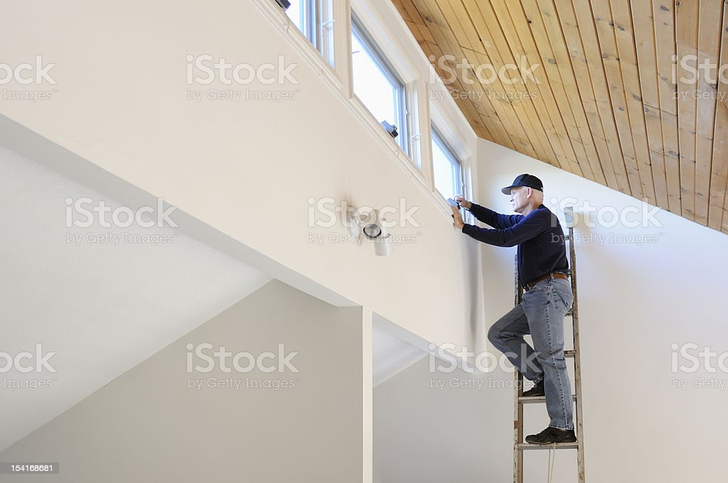 Worker on Ladder stock photo