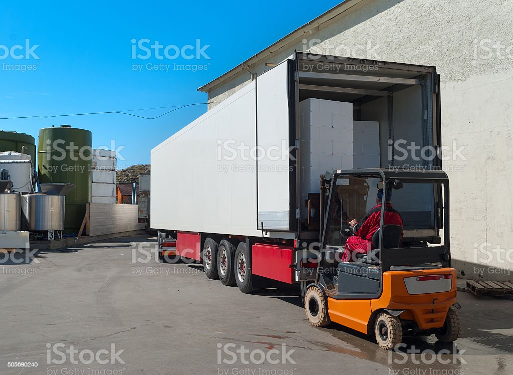 Worker on loader loads white semi-truck stock photo