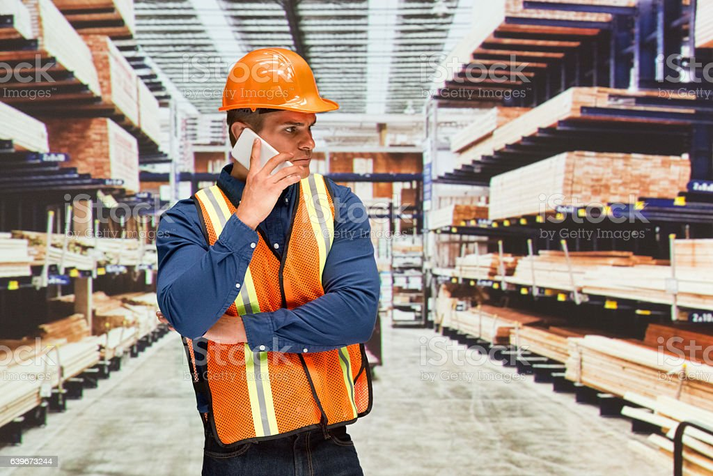 Worker on phone in warehouse stock photo