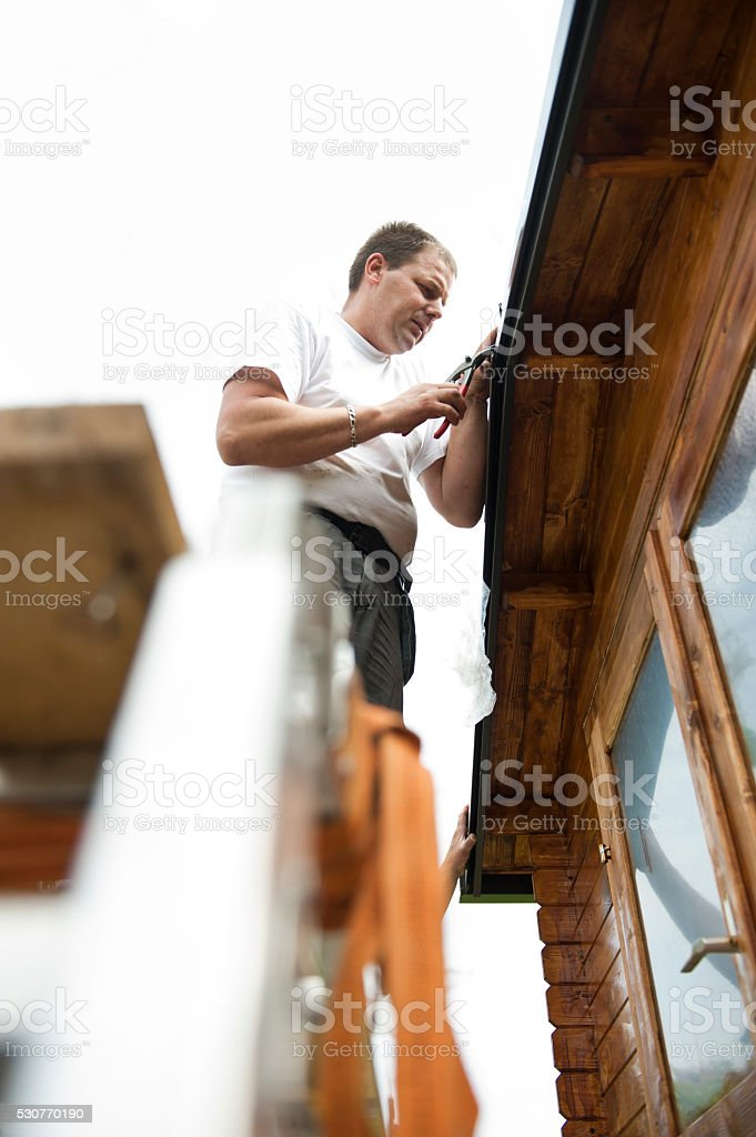 Worker on roof  installing metal tile stock photo