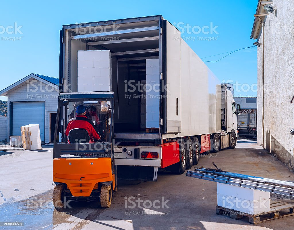 Worker on the loader loads long white semi-trailer stock photo