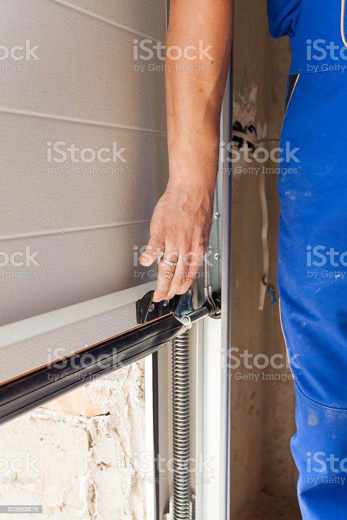 Worker open a garage door during installation stock photo