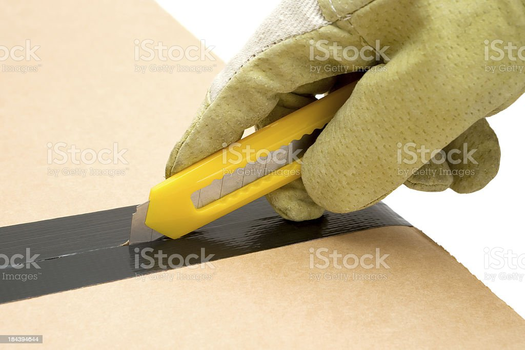 Worker Opening a Cardboard Box stock photo