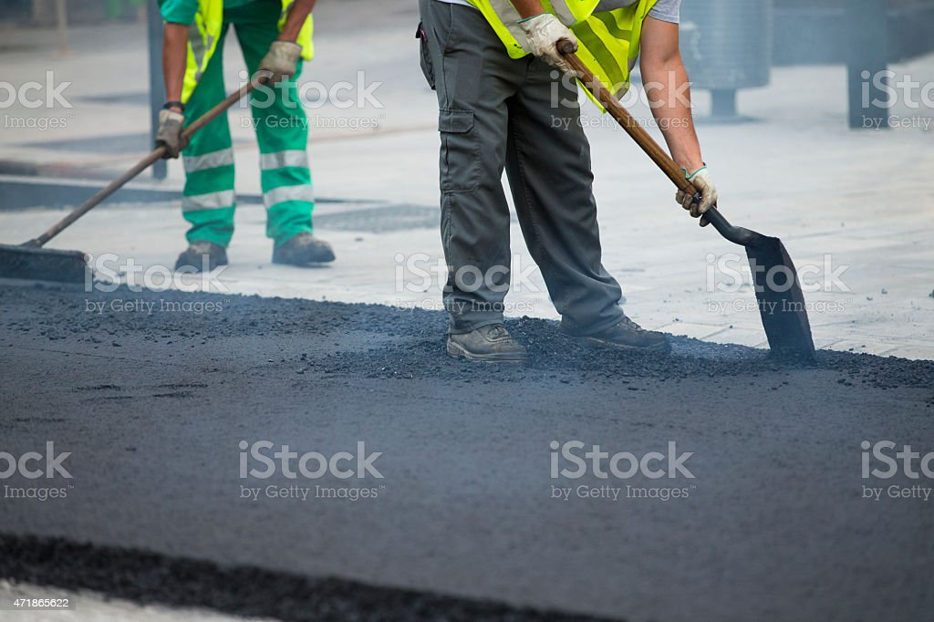 Worker operating asphalt paver machine during road construction stock photo