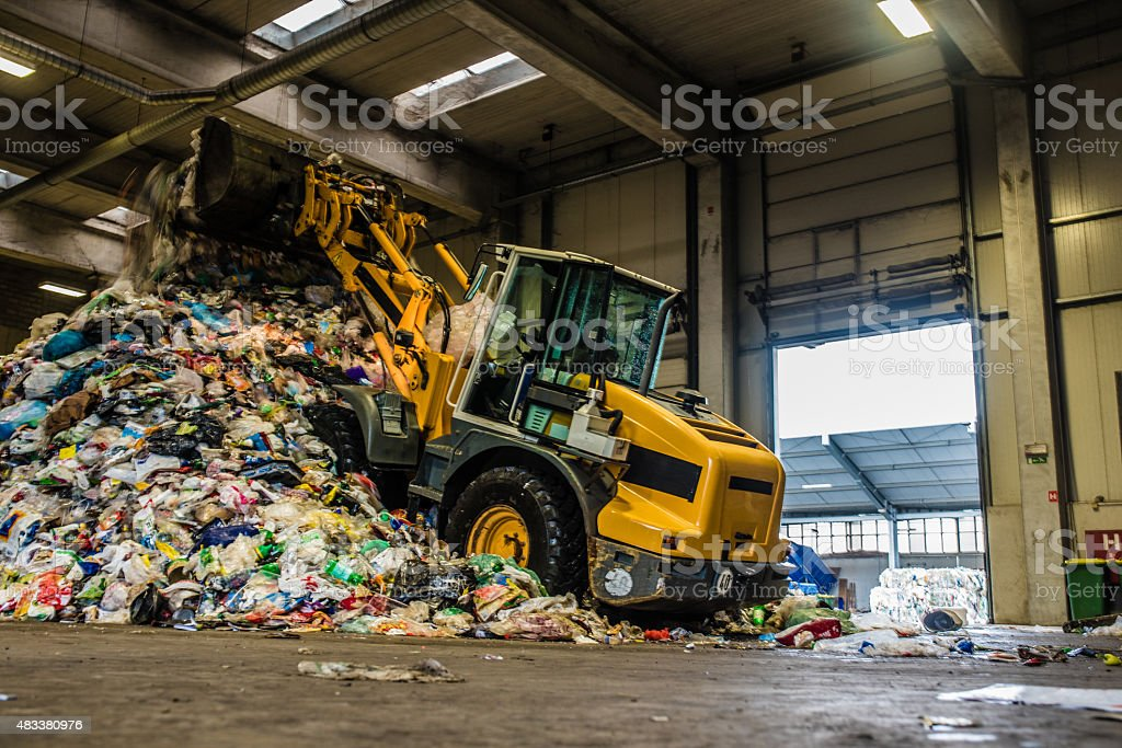 Worker operating bulldozer at recycling plant stock photo