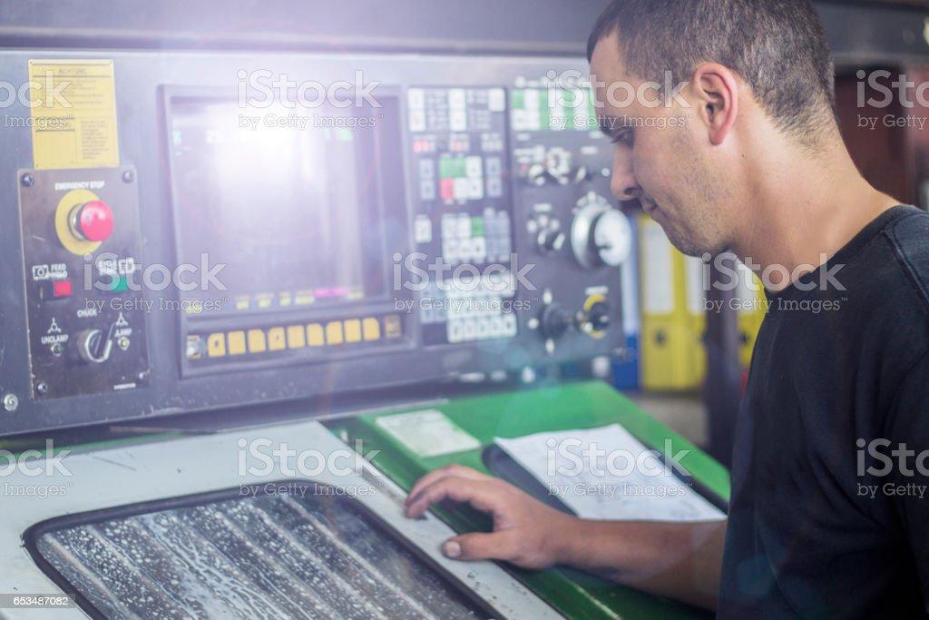 Worker operating CNC machine stock photo
