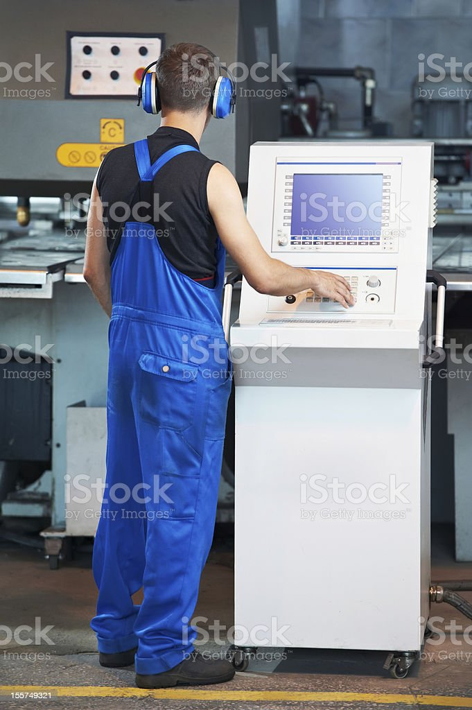 worker operating cnc punch press royalty-free stock photo