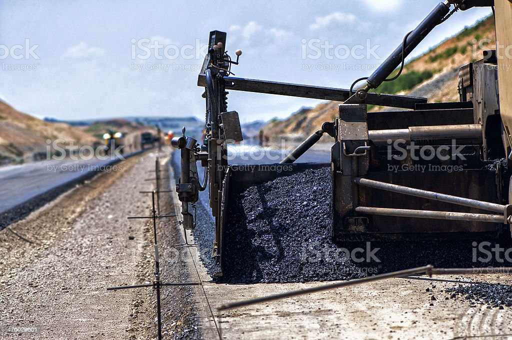 Worker operating industrial asphalt paver machine during highway stock photo