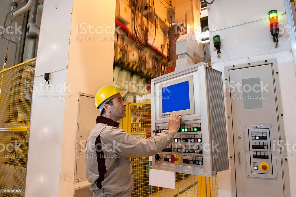 Worker operating press machine for automotive stock photo