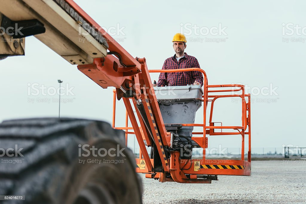 Worker operating Straight Boom Lift stock photo
