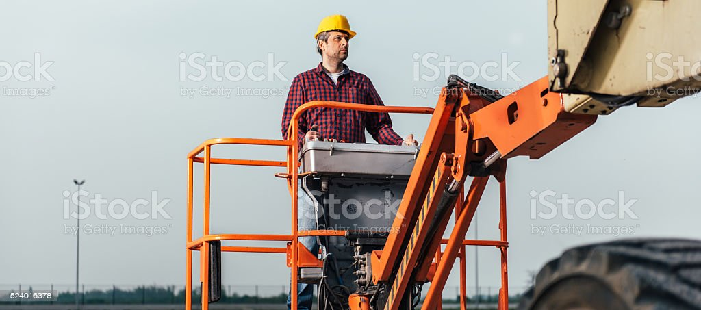 Worker operating Straight Boom Lift stock photo