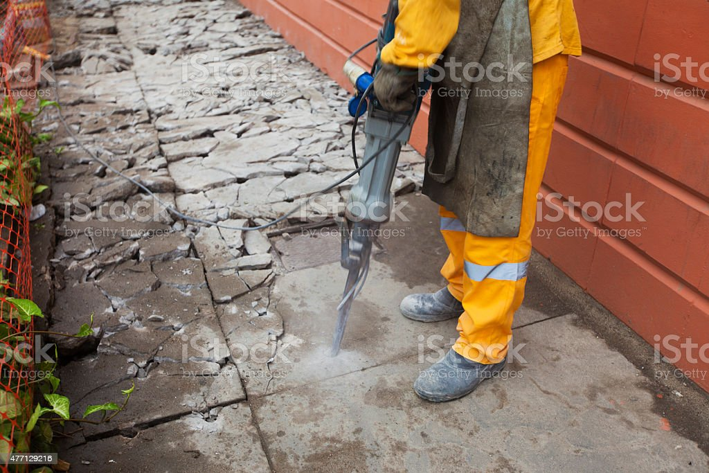 Worker operating the stone breaker stock photo