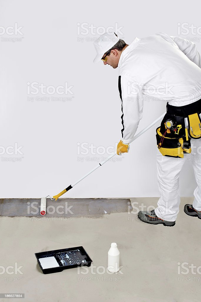 worker paint with primer concrete floor for waterproofing royalty-free stock photo