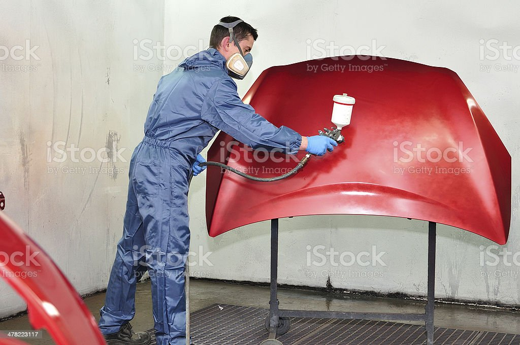 Worker painting a red bonnet. stock photo