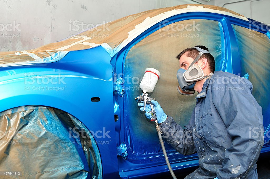 Worker painting blue car. stock photo