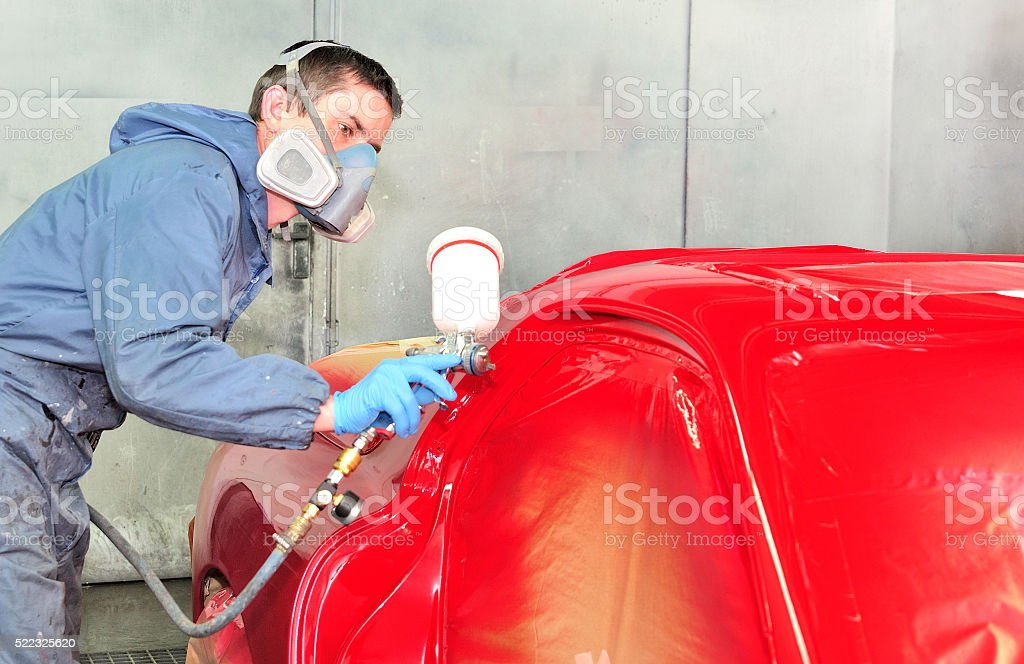 Worker painting red car. stock photo