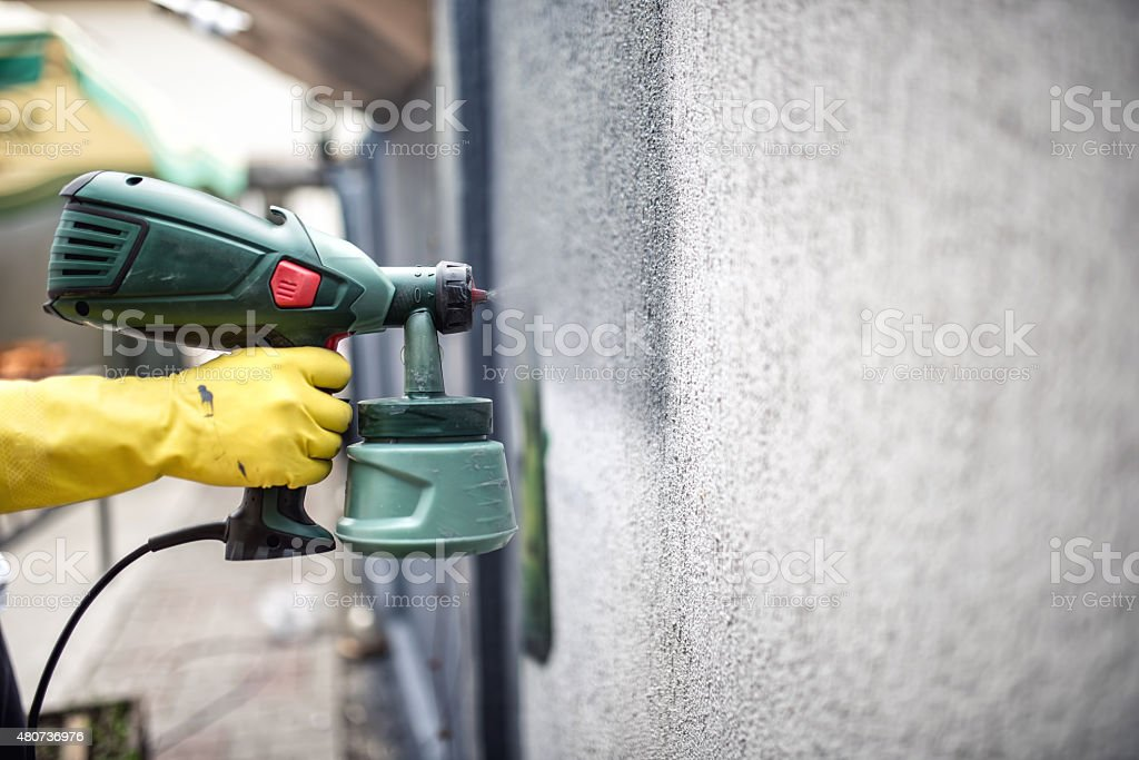 Worker painting wall with grey paint using professional spray gun stock photo