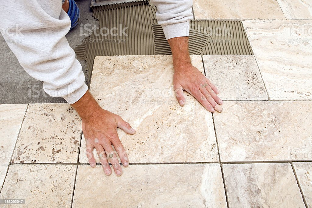 Worker Places New Tile on a Bathroom Floor royalty-free stock photo