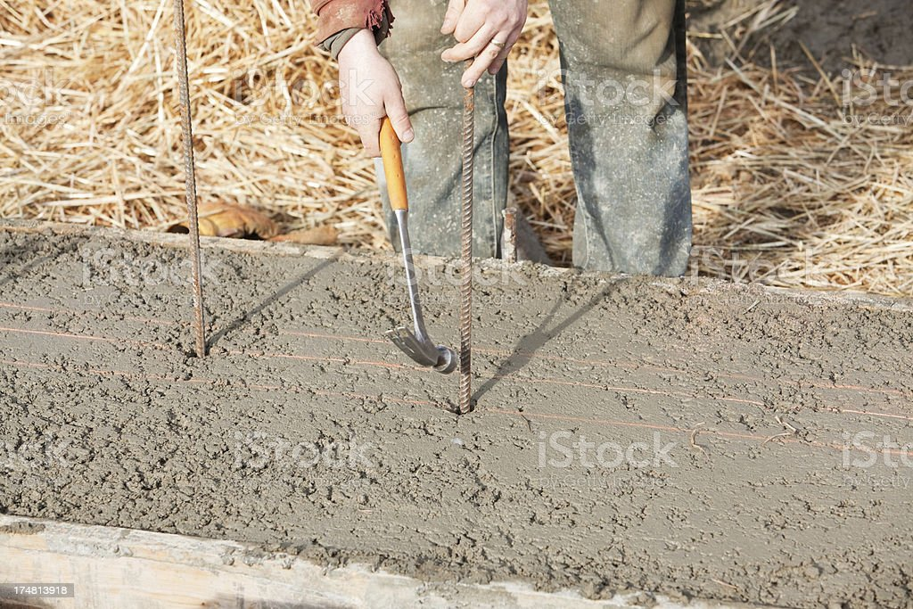 Worker Placing Rebar into Concrete House Footing royalty-free stock photo