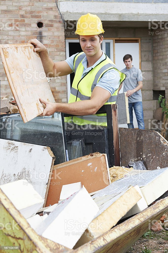 Worker placing rubble into waste container stock photo