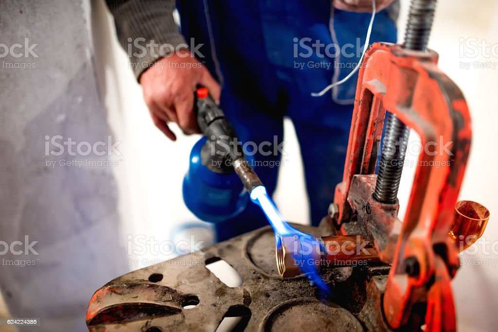 worker, plumber using blowtorch for soldering copper fittings stock photo