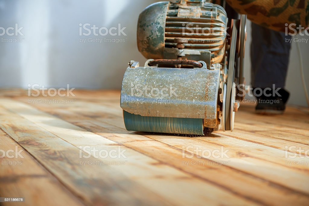 Worker polishing parquet floor with grinding machine stock photo