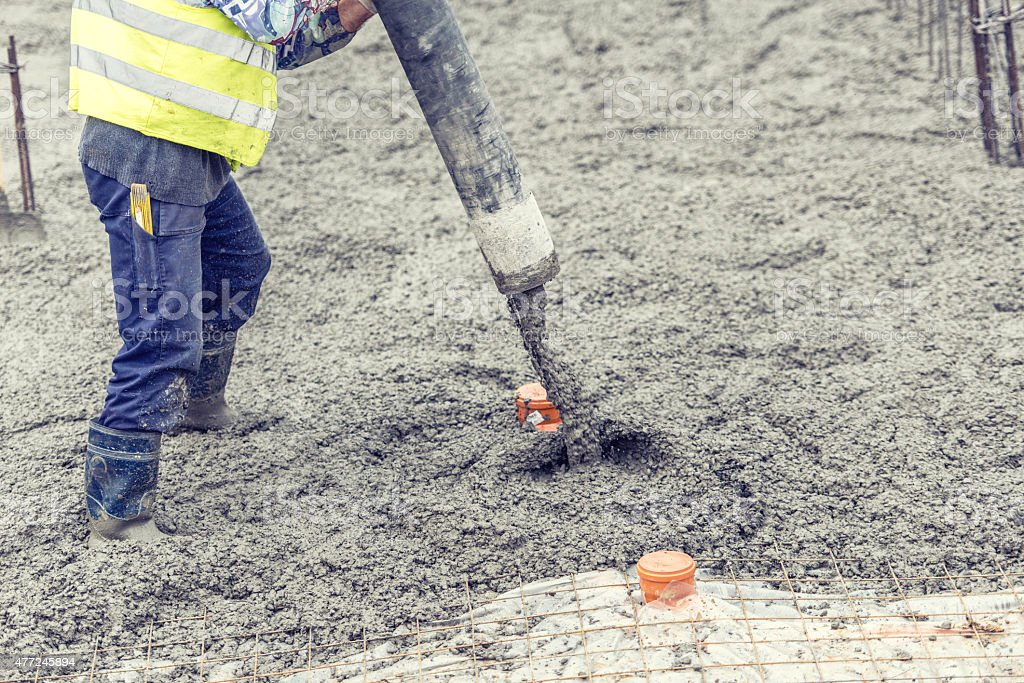 worker pouring concrete, directing the pump and working in foundation stock photo