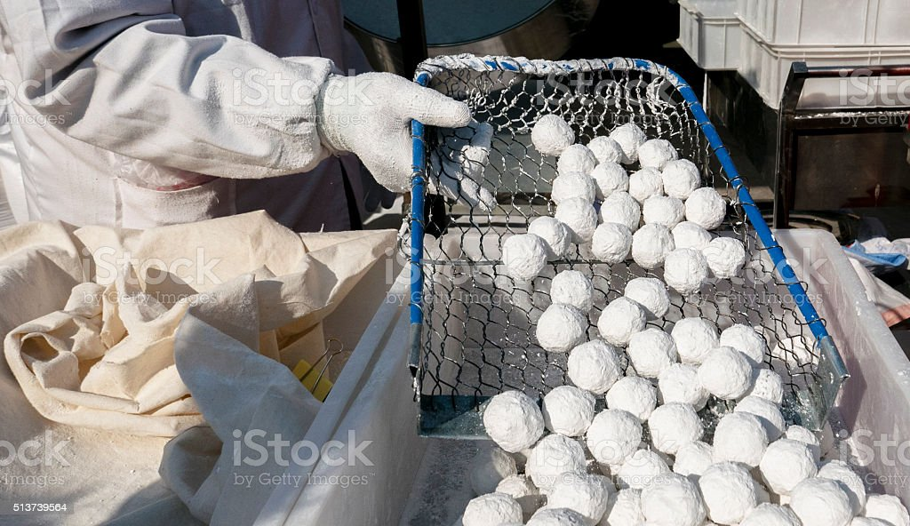 worker pouring glutinous rice balls into container stock photo