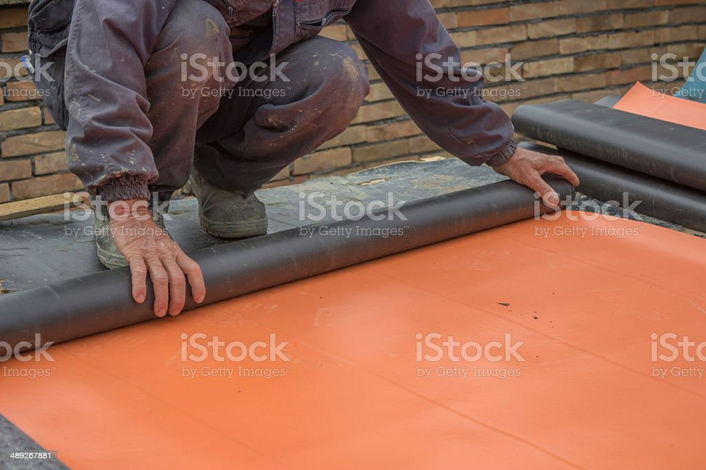 Worker preparing insulation material for basement wall 3 stock photo