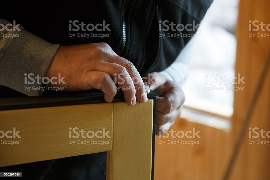 Worker preparing to install new three pane wooden windows stock photo
