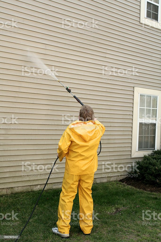 A worker pressure washing the siding of a house stock photo