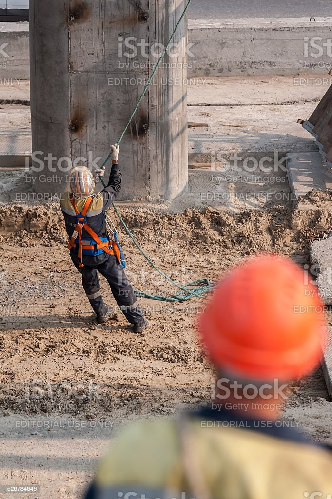 Worker pulls rope to level panel lifted by crane stock photo