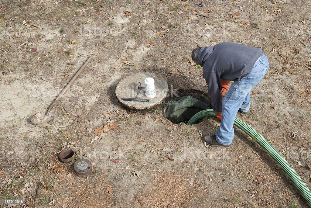 Worker Pumps Residential Septic Tank for Home Improvement stock photo